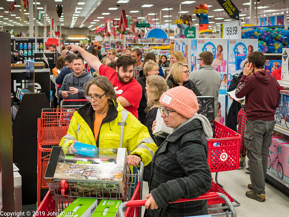 """28 NOVEMBER 2019 - ANKENY, IOWA: Shoppers crowd an aisle between the electronics and toy departments at the Target store in Ankeny, Iowa, Thursday evening. """"Black Friday"""" is the unofficial start of the Christmas holiday shopping season and has traditionally thought to be one of the busiest shopping days of the year. Brick and mortar retailers, like Target, are facing increased pressure from online retailers this year. Many retailers have started opening on Thanksgiving Day. Target stores across the country opened at 5PM on Thanksgiving to attract shoppers with early """"Black Friday"""" specials.    PHOTO BY JACK KURTZ"""