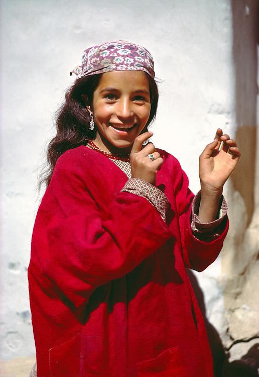 A young Kashmiri girl smiles as she playfully ducks away from the camera near Srinagar, India.