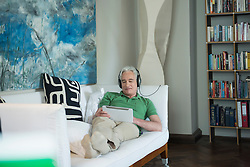 Mature man with headset and digital tablet sitting on couch, smiling