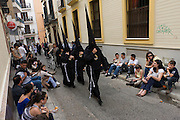 Hooded peninitents (Nazarenos) during Seville's annual Easter Holy Week (Semana Santa de Sevilla) one of the most important traditional events of the city. The annual celebrations mark the story of Christ's crucifixion and the Nazarenos walk through the historic Andalucian city in front of the devout in a series of processions. Several hundred members of the 57 religious brotherhoods (or Hermandades) from many of city churches accompany giant floats (Pasos) depicting the road to Calvary. The brotherhoods (founded in the mid 14th century) are associations of Catholic laypersons organised for the purpose of performing public acts of religious observance; in this case, related to the Passion and death of Jesus Christ and to perform public penance.