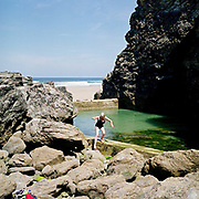 "After her daily swim, an elderly local woman climbs out of Porthtowan Pool, Cornwall, UK. A beautifully wild tidal pool surrounded by cliffs and rocks, with a retaining concrete wall. ""Weekdays are nicer, on weekends you get all the young ones coming and throwing themselves in, they don't swim"". Until the 1950s and the rise of the heated indoor swimming pool, children learnt to swim outdoors. For those close to the sea, many man-made tidal swimming pools were constructed around Britain's coastline. Heated by the sun, these tidal pools were often built to keep bathers safe from high and rough seas, which explains why so many of them are clustered in Scotland and around the surfing beaches of Cornwall. Whether they are simple swimming holes made by shoring up natural rock pools or grand lido-like pools complete with lifeguards and tea huts, they are all refreshed by good high tides."