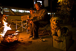 Homeless day laborers warm themselves up by fire in Kamagasaki, Japan.