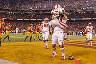 Ameer Abdullah is hoised in the air by an offensive lineman following a score against USC in the 2014 Holiday Bowl. © Aaron Babcock