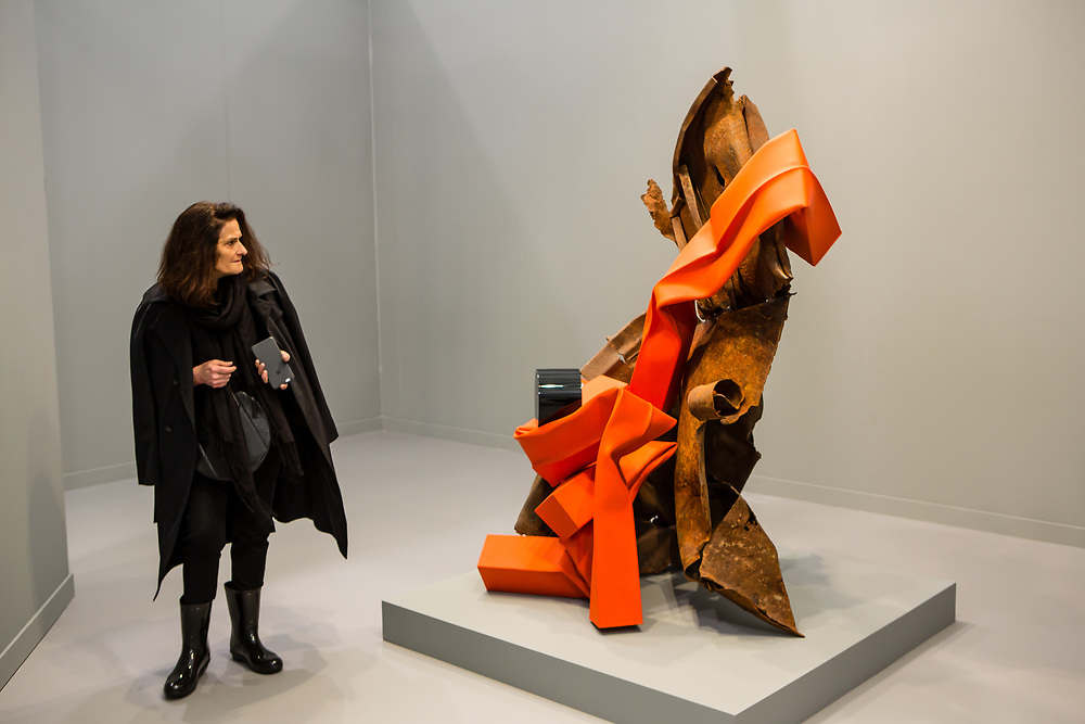 """New York, NY - 5 May 2017. The opening day of the Frieze Art Fair, showcasing modern and contemporary art presented by galleries from around the world, on Randall's Island in New York City. A woman casts a critical eye on Carol Bove's sculpture """"Prélude à l'apres-midi d'une faune."""" 2017, in the David Zwirner gallery."""