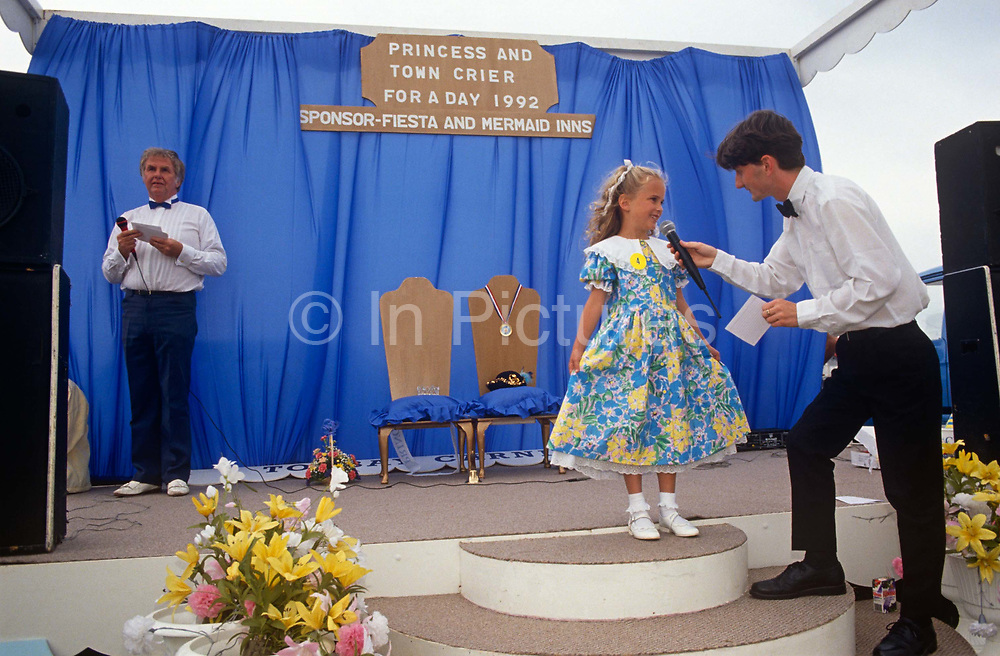 A contestant for the next Torbay Carnival Princess and Queen is interviewed by a man as the competition thrones await their newest occupants during the seaside town's fair in Devon, England. A crown, hat and two bouquets of flowers are for the young girls too. The theme of the stage is blue, with matching colours on both cushions and the backing curtain (drapes). We get a sense of the tacky and the old-fashioned nature of the carnival and of its princess competition.
