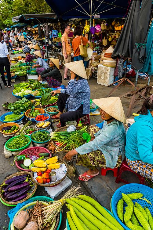 Women selling produce at outdoor market, Central Market, Hoi An, Vietnam.