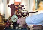 """© Licensed to London News Pictures. 23/10/2014. Guildford, UK. Michael Tooke changes the time mechanism on a turret clock.  clock in the shop. As British Summer Time comes to an end, staff at Horological Workshops start the task of changing the 100's of clocks at their store in Guildford, Surrey, UK. Michael Tooke who has owned the store for over 40 years and worked in the clock business all his life said. """"at this time of year we get a lot of people who bring clocks in for repair after they have changed the time incorrectly by winding back the hands manually"""".Clocks change on Sunday morning 26th October. Photo credit : Stephen Simpson/LNP"""