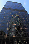 The Swiss Re Building (Gherkin) is reflected in a building opposite, in the City of London