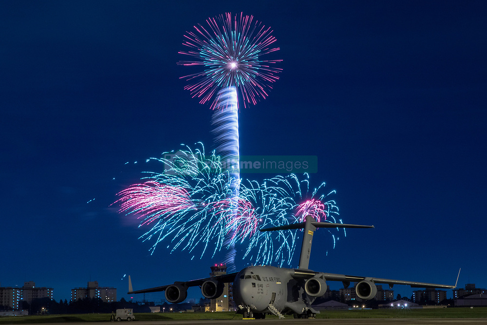 Fireworks explode behind a U.S. Air Force C-17 Globemaster III aircraft assigned to the 15th Wing during Celebrate America, July 3, 2018, at Yokota Air Base, Japan. Celebrate America is an annual event that provides military members and their families the opportunity to enjoy games, food and bands before culminating in a fireworks display over the Yokota AB airfield to celebrate Independence Day. (U.S. Air Force photo by Yasuo Osakabe)