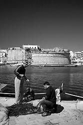Pescatori gallipolini controllano, sistemano e riparano le reti, attrezzi indispensabili per le loro attività. Di fronte a loro la splendida vista sul Rivellino.