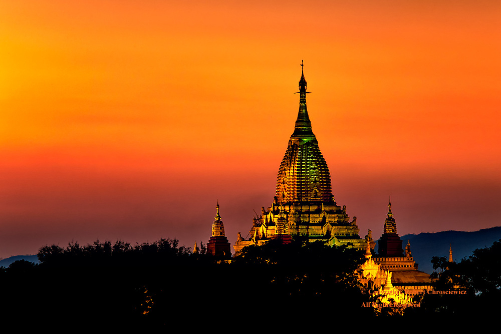 Buddhist Gold and Peach: The illuminated Buddhist Ananda Temple shines as a golden jewel, set against the peach-golden sky, Bagan Myanmar.