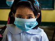 """22 JANUARY 2018 - GUINOBATAN, ALBAY, PHILIPPINES: Students at Muladbucad Grande Elementary School in Guinobatan wear face masks in their 1st grade class. Several communities in Guinobatan were hit ash falls from the eruptions of the Mayon volcano and many people wore face masks to protect themselves from the ash. There were a series of eruptions on the Mayon volcano near Legazpi Monday. The eruptions started Sunday night and continued through the day. At about midday the volcano sent a plume of ash and smoke towering over Camalig, the largest municipality near the volcano. The Philippine Institute of Volcanology and Seismology (PHIVOLCS) extended the six kilometer danger zone to eight kilometers and raised the alert level from three to four. This is the first time the alert level has been at four since 2009. A level four alert means a """"Hazardous Eruption is Imminent"""" and there is """"intense unrest"""" in the volcano. The Mayon volcano is the most active volcano in the Philippines. Sunday and Monday's eruptions caused ash falls in several communities but there were no known injuries.    PHOTO BY JACK KURTZ"""