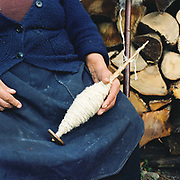 An elderly Romanian peasant holds a spindle of wool spun from her own sheep, Botiza, Maramures, Romania. Traditionally subsistence farmers In Maramures raise their own sheep to provide wool for knitting and weaving clothing.