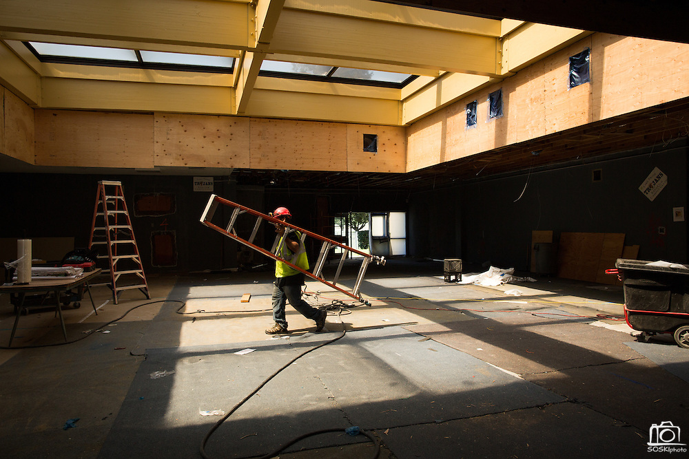 A construction worker carries a ladder through the Milpitas High School cafeteria and library renovation areas at Milpitas High School in Milpitas, California, on July 18, 2014. (Stan Olszewski/SOSKIphoto)