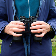 A birdwatcher holds a pair of binoculars, North York Moors National Park, North Yorkshire, UK