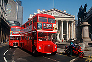 Two red London Routemaster buses drive along 1990s Threadneedle Street in the City of London aka The Square Mile, the capitals financial centre, on 18th February 1992, in London, England.