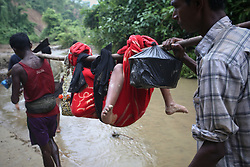 September 5, 2017 - Cox'S Bazar, Bangladesh - A Rohingya child is carried on a sling while his family walk throuh hill after crossing the border into Bangladesh near Cox's Bazar's Teknaf area, Tuesday.  A total of 87,000 mostly Rohingya refugees have arrived in Bangladesh since violence erupted in neighbouring Myanmar on August 25, the United Nations said today, amid growing international criticism of Aung San Suu Kyi. Around 20,000 more were massed on the border waiting to enter, the UN said in a report. (Credit Image: © Mushfiqul Alam/NurPhoto via ZUMA Press)