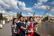 "A family from Asia  visiting Charles Bridge and documenting their visit with a ""smart phone"" on a selfie stick. The Charles Bridge (Czech: Karlův most) is a famous historic bridge that crosses the Vltava river in Prague, Czech Republic and is probably the Nr.1 tourists magnet in the city."