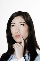 studio shot portrait of a beautiful southeast asian young woman pensive