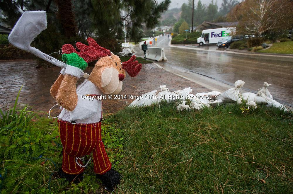 12月2日,美國加利福尼亞州洛杉磯,在民居前看到的聖誕裝飾和沙包。當天南加州迎來秋天第一場暴雨,將為今年面臨嚴重乾旱問題的加州帶來2至5寸雨水。 同時,當局亦發出警告,洪水、土石流可能會襲擊部分地區。 (新華社發 趙漢榮攝) <br /> Sandbags and the Christmas decorations on a lawn are seen in Los Angeles, California, Tuesday, December 2, 2014. California is bracing for the arrival of a new, more powerful Pacific storm following a weekend of scattered rain, showers and snow. The National Weather Service says a low-pressure system off the coast will draw a plume of subtropical moisture northward into the state beginning on Tuesday.  (Xinhua/Zhao Hanrong)(Photo by Ringo Chiu/PHOTOFORMULA.com)