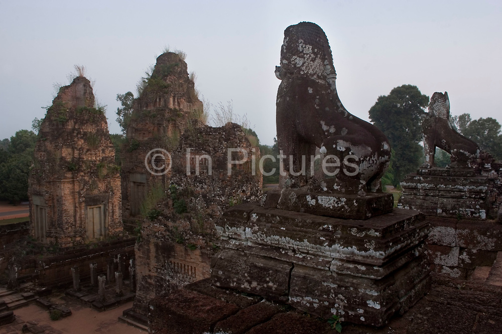 """Pre Rup, which means """"turning the body"""" in reference to a cremation ritual, is a tall grand towered temple made from laterite and brick. Pre Rup is a state-temple of Rajendravarman II, and was consecrated to Shiva in 962. Stone lions guard each of the four stair cases which lead up the temple, as they stand looking out over the surrounding green paddy fields."""