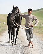 Berdi, head groom at the President of Turkmenistan's Ahal Teke horse complex outside Ashgabat, with a black Ahal Teke stallion