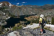 Hiker overlooking Heather Lake in the high alpine mountains of Desolation Wilderness, El Dorado National Forest, California