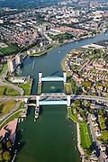 Nederland, Zuid-Holland, Krimpen aan den IJssel, 28-09-2014; stormvloedkering in de Hollandsche IJssel. Bij storm en dreigend hoog water wordt een van de twee schuiven naar beneden gelaten, de tweede schuif dient al reserve. De scheepvaart kan de gesloten kering paseren via de naastgelegen schutsluis. De stormvloedkering maakt deel uit van de Deltawerken en is als eerste voltooid in 1958. Ten tijde van De Ramp - watersnood 1953 - werd het zeewater door de storm opgestuwd en dreigde de verzwakte rivierdijken in het achterland het te begeven waardoor grote van het laag gelegen westen van Nederland ondergelopen zouden zijn.<br /> Krimpen at the river IJssel, near Rotterdam: storm surge barrier, protects the highly populated western part of Holland, which lies below sea level. In case of storm and threat of high water, one of the two doors is lowered into the river (the second door is a spare one). The lock next to the barrier allows shipping when the barrier is closed.<br /> luchtfoto (toeslag op standard tarieven);<br /> aerial photo (additional fee required);<br /> copyright foto/photo Siebe Swart