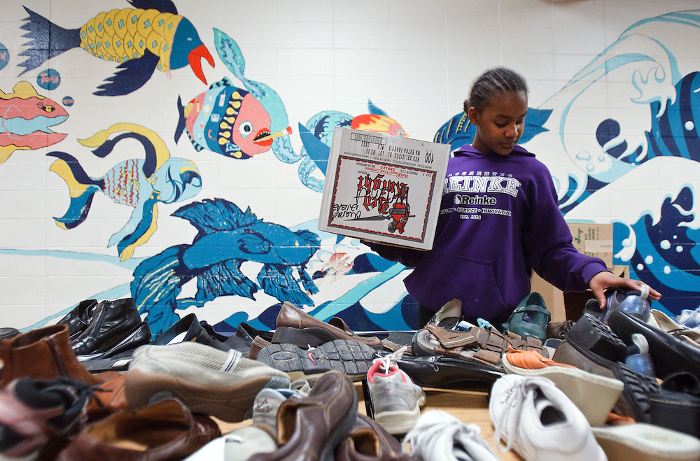 """Sixth-grader Angella Banzi seaches through a sea of shoes during Christmas Shopping Night Friday at Walnut Middle School. Students created wish lists which they submitted to their teachers who then donated gifts so the kids could """"shop"""" for others. (Independent/Matt Dixon)"""