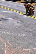Artist drawing on road at the Amgen Tour of California, Santa Monica Mountains, California