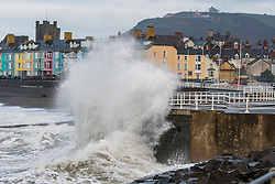 © Licensed to London News Pictures. 21/12/2016. Caberystwyth, Wales, UK. On the shortest day of the year, the Winter Solstice, a change in the weather brings showers of rain and  gusty winds combined with the  high tide to drive huge waves to batter the seafront and harbor wall at Aberystwyth on the Cardigan Bay coast of the Irish Sea in West Wales UK. Photo credit: Keith Morris/LNP
