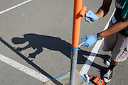 Peter Piczon, 17, of Silver Creek paints a tetherball pole during Comcast Cares Day at Curtner Elementary School in Milpitas, California, on April 27, 2013. (Stan Olszewski/SOSKIphoto)