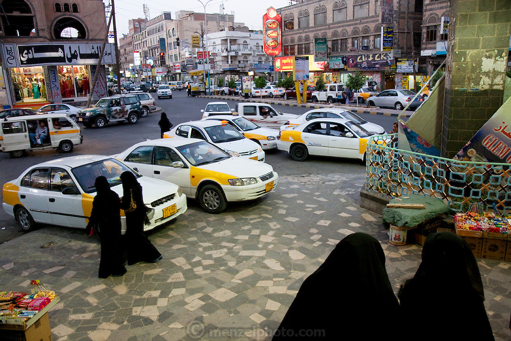 Women wearing burqas walk on a street in the newer section of Sanaa, the capital of Yemen. Most Yemeni women cover themselves for modesty, in accordance with tradition.