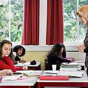 Nederland Rotterdam 23-09-2009 20090923 Serie over onderwijs,   openbare scholengemeenschap mavo, havo en vwo. Lesuur in klaslokaal, lerares geeft klassikaal  toelichting op de lesstof en stelt de leerlingen vragen.                                              .Foto: David Rozing