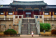 A small child in a sunhat strolling in front of the imposing Pulguksa Temple in South Korea
