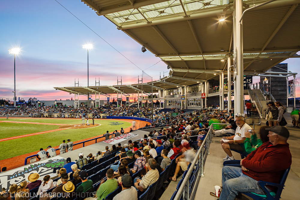 Along the third baseline, fans watch a minor league baseball game as the sun sets and lights up the sky with pink and magenta hues.