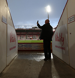 A supporter uses his mobile phone before the game between Bournemouth and Brighton and Hove Albion