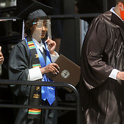 Oceania Alexis Mack, center, wears a face shield while receiving her baccalaureate degree during the commencement ceremony at Doyt Perry Stadium at Bowling Green State University in Bowling Green, Ohio, on Saturday, May 1, 2021. THE BLADE/KURT STEISS