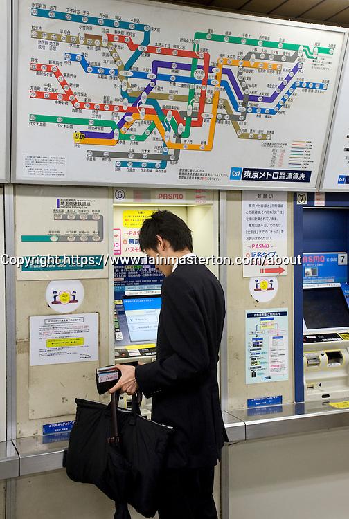 Man buying ticket for subway train in Tokyo Japan