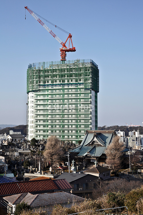 new high rise under construction with in the foreground low rise residential housing and a traditional old Japanese temple complex Yokosuka Japan
