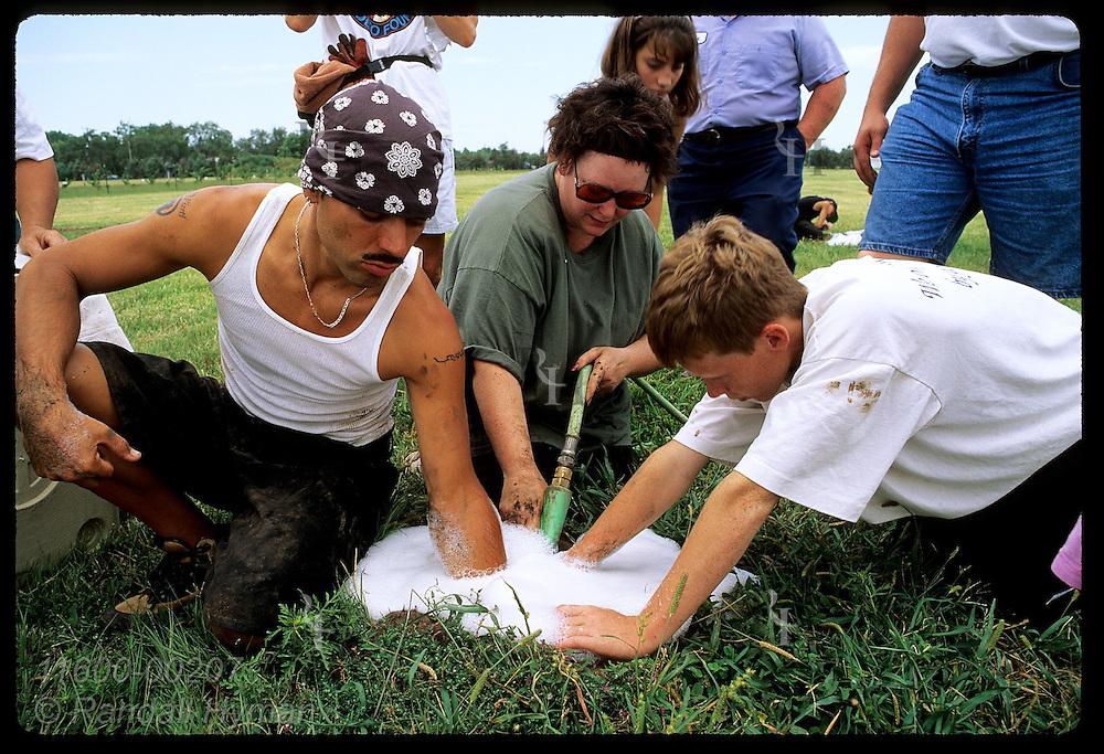 PECA's Jarid Manos & local volunteers reach into soapy burrow to catch prairie dogs; Hutchinson. Kansas