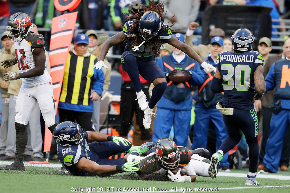 Seattle Seahawks cornerback Shaquill Griffin (26) leaps over Tampa Bay Buccaneers quarterback Jameis Winston (3) as Winston goes down next to Seahawks outside linebacker K.J. Wright (50) during the second half of an NFL football game, Sunday, Nov. 3, 2019, in Seattle. The Seahawks won 40-34. (AP Photo/John Froschauer)