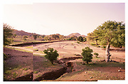 """NUBA MOUNTAINS, SUDAN – JUNE X, 2018: CAPTION<br /> <br /> In 2011, the government of Sudan expelled all humanitarian groups from the country's Nuba Mountains. Since then, the Antonov aircraft has terrorized the Nuba people, dropping more than 4,080 bombs on hospitals, schools, marketplaces and churches. Today, vestiges of the Antonov riddle the landscapes of daily life, where more than 1 million Nuba live in famine conditions – quietly enduring the humanitarian blockade intended to drive them out of the region. The skies are mostly clear. Yet the collective memory of the bombings remains an open wound, and the Antonov itself a persistent threat. So frequent were the attacks that the Nuba nicknamed the high flying aircraft and its dismal hum: """"Gafal-nia ja,"""" they would declare, running to the hillsides. """"The loss of appetite has come."""""""