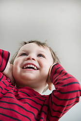 Boy covering ears, smiling