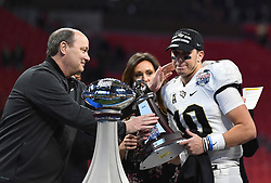 UCF Knights quarterback McKenzie Milton (10) accepts a trophy from Gary Stoken after the second half of the Chick-fil-A Peach Bowl NCAA college football game between Auburn University and the University of Central Florida, January 1, 2018, in Atlanta. UCF won 34-27 to go undefeated for the season. (David Tulis via Abell Images for Chick-fil-A Peach Bowl)