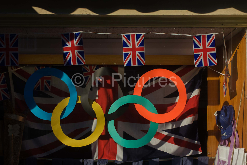 Misuse of the copyrighted Olympic ring brand in a shop window at the Suffolk seaside town of Southwold, Suffolk. We see a detail of the rings that have been cut out and suspended on the window that otherwise shows union jack flags and clothing at this traditional English seaside resort that lacks advertising and branding, the day before the opening of the London 2012 Olympic opening ceremony.