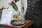Champagne celebration crossing the Arctic Circle heading south, Norway on Hurtigruten ferry ship, officer pouring from bottle into glasses