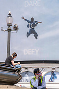 An image of a leaping figure from a Piccadilly Circus Calvin Klein ad whose slogan is Dare to Defy, and resting Londoners on Freedom Day. This date is what Prime Minister Boris Johnsons UK government has set as the end of strict Covid pandemic social distancing conditions with the end of mandatory face coverings in shops and public transport, on 19th July 2021, in London, England.