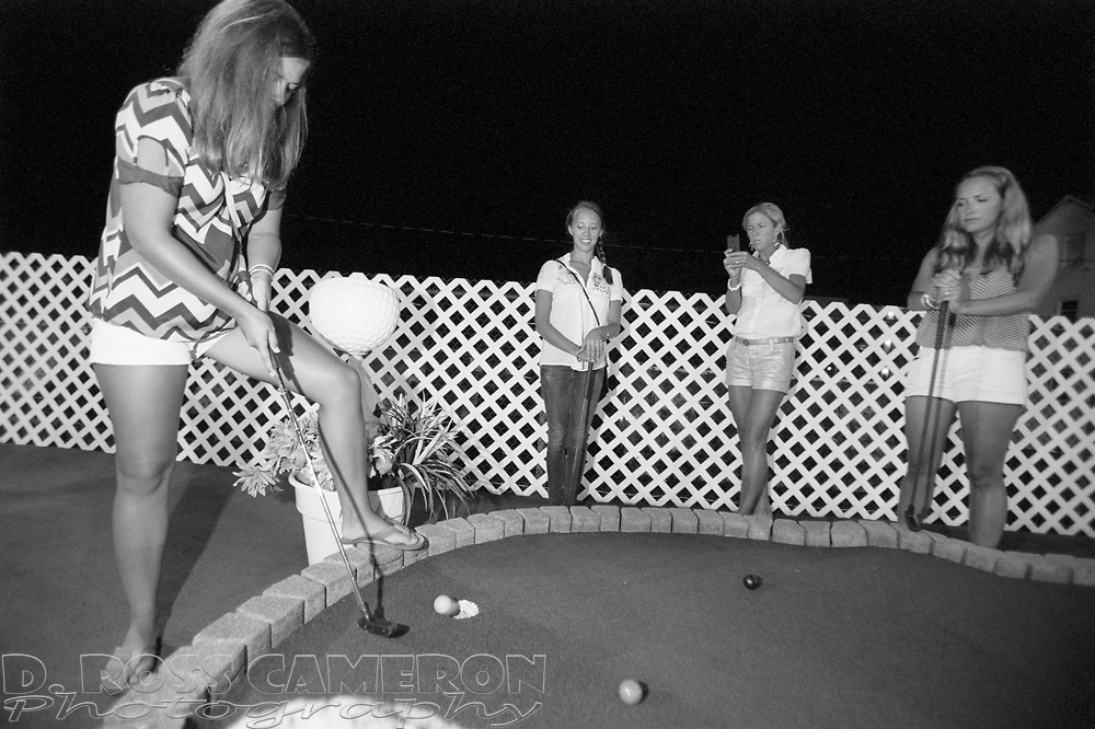 Sarah Cameron, left, prepares to putt while Jayne SullyCole, Sarah's mother Ann Cameron and cousin Dana Del Galdo look on, during a miniature golf tournament, Saturday, July 27, 2013 on the boardwalk in Rehoboth Beach, Del. (Photo by D. Ross Cameron)