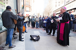 © Licensed to London News Pictures. 25/3/2016. Birmingham, UK. Good Friday Walk of Witness. Churches in Birmingham come together to walk through Birmingham City Centre, visiting Cathedrals and Churches.<br /> Pictured, the procession pauses to be entertained by buskers on New Street. Photo credit : Dave Warren/LNP